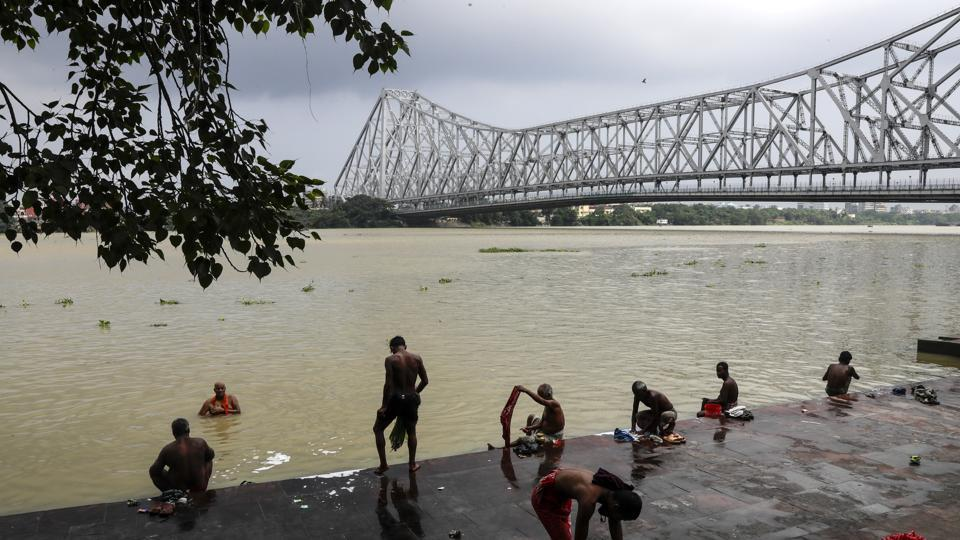 People take bath on the bank of Hooghly River beside Howrah Bridge during West Bengal state lockdown to prevent the spread of coronavirus in Kolkata.