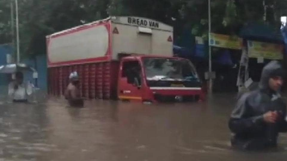 People wading through waist-deep water after heavy rainfall in Parel East.