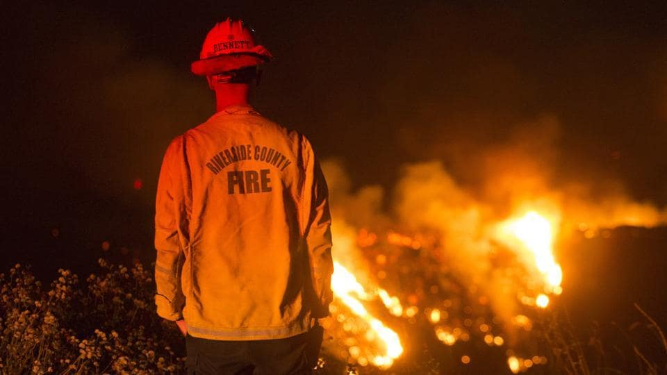 A firefighter watches a brush fire at Banning in California on August 1. A wildfire in mountains east of Los Angeles that has forced thousands of people from their homes was sparked by a malfunctioning diesel vehicle, fire officials told AP on August 3.  (Ringo H.W. Chiu / AP)