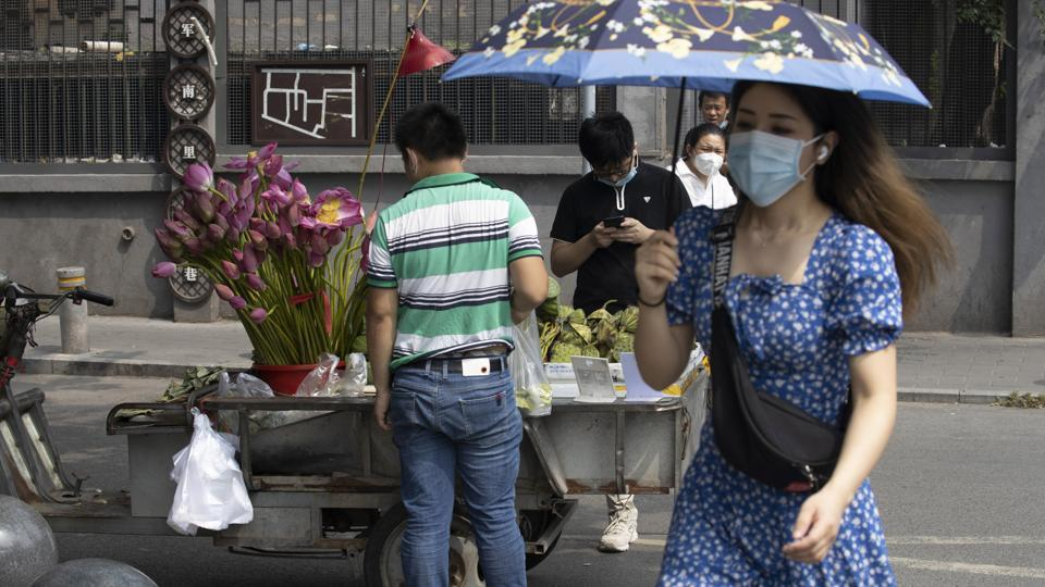 A woman wearing a mask to curb the spread of the coronavirus walks past a street vendor selling lotus flowers and seeds in Beijing on Frida.