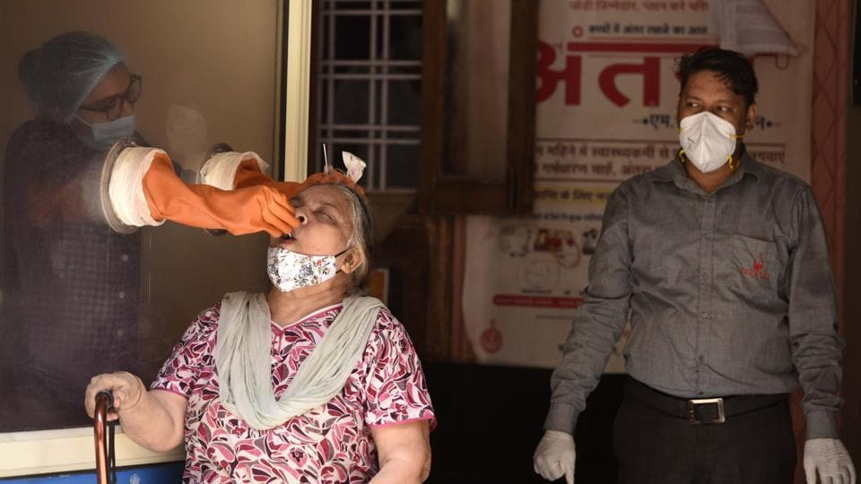 A health worker collects a swab sample from a woman for coronavirus test, at Urban Primary Health Centre,  Gurugram
