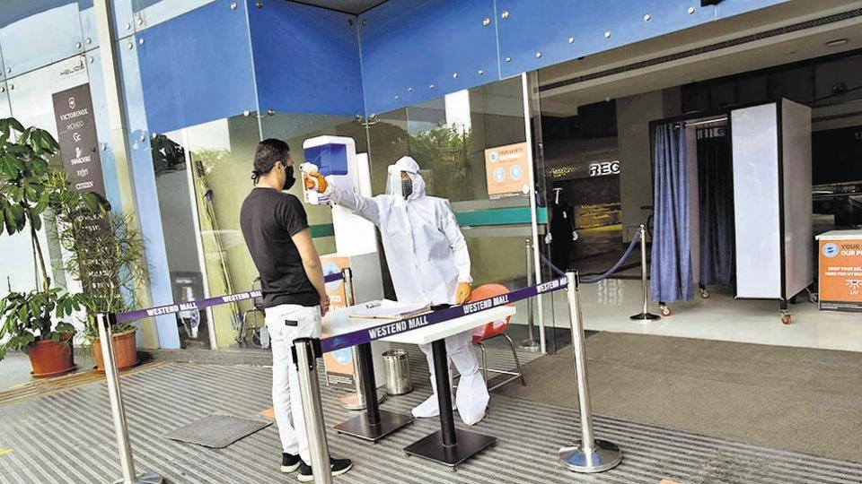 A visitor at the Westend mall at Aundh undergoes thermal checking at the gate on August 3.