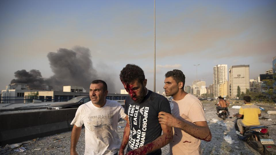 People help a man wounded in a massive explosion in Beirut, Lebanon.