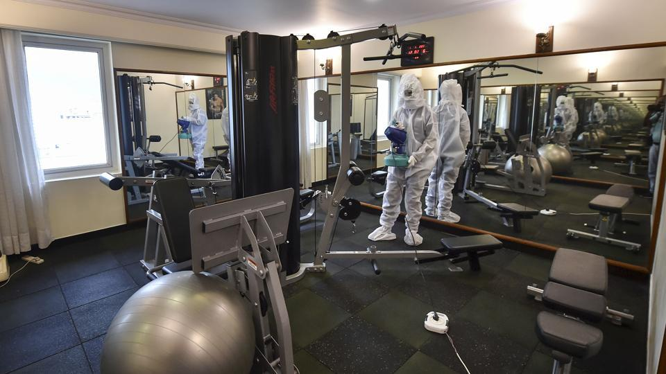 A worker wearing a PPE kit sanitizes a gym at Peerless Inn hotel ahead of its reopening for the guests, during Unlock 3.0, in Kolkata.