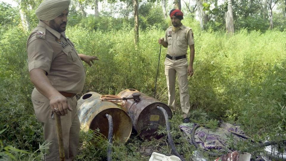 Police personnel with recovered stills near Sutlej river in Ludhiana on Tuesday.