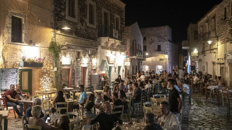 Tourists and local residents sit outside taverns in the town of Areopoli on the Mani Peninsula, Laconia, Peloponnese region, Greece on Wednesday July 29, 2020. Some travelers from Europe's wealthier north appear more inclined to stay closer to home on concerns about coronavirus infections, which is a potential blow to countries like Spain, Italy and Greece, where tourism accounts for a big chunk of their economies. (Konstantinos Tsakalidis/Bloomberg)