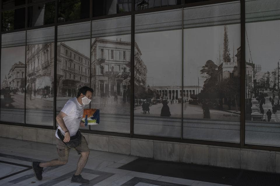 A man wearing face mask runs next to a bank headquarters in Athens, on Tuesday, Aug. 4, 2020. Greek authorities introduced tougher restrictions the last days following an increase in infections.(AP Photo/Petros Giannakouris.