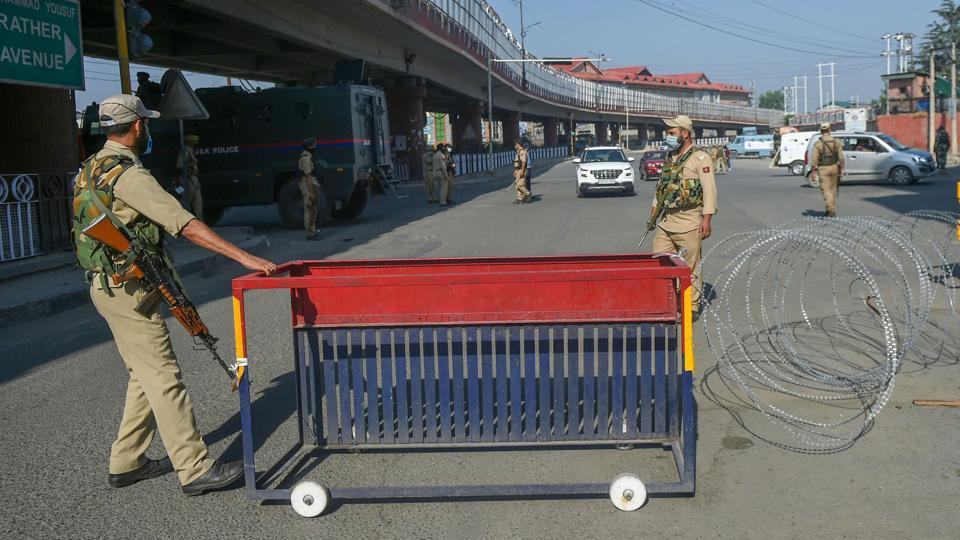 Security personnel place a barricade on a street during the restrictions imposed on the first anniversary of revocation of the special status of Jammu and Kashmir, in Srinagar on Wednesday.