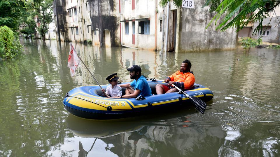 Air India employees enjoy in flooded water during heavy rain at Air India colony in Mumbai.
