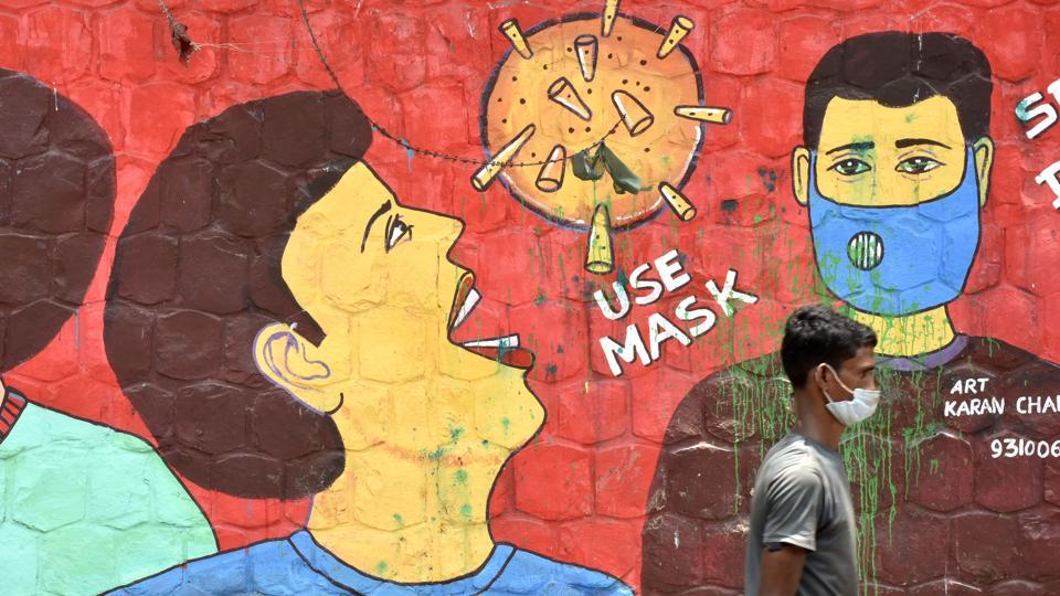 A man wearing a face mask crosses a mural on the use of face masks as protection against the coronavirus, at Jamia Nagar in New Delhi on August 4. India's tally of the coronavirus disease (Covid-19) has risen to more than 1.9 million after a seventh consecutive day of over 50,000 being recorded in the last 24 hours, Union health ministry data showed on August 5. (Vipin Kumar / HT Photo)