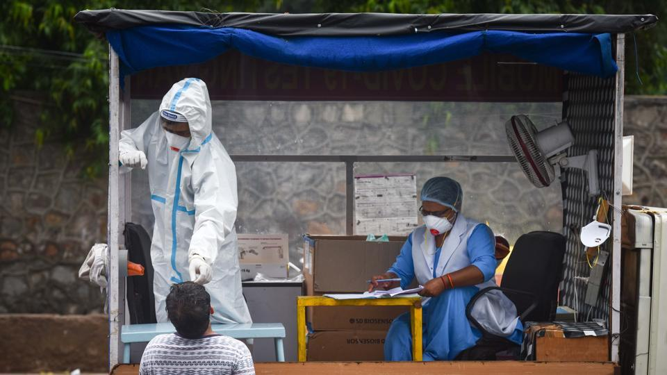 A healthcare worker in PPE coveralls collects a swab sample from a man for coronavirus rapid antigen test, at Daryaganj, in New Delhi, on Wednesday.
