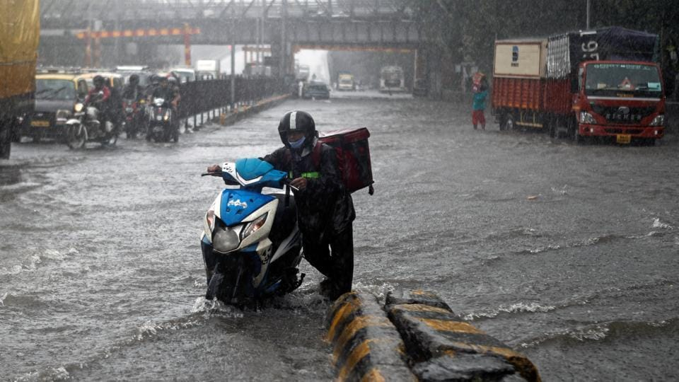 A delivery boy pushes his scooter after it stopped working along a waterlogged road following heavy rainfall in Mumbai on  August 5, 2020.