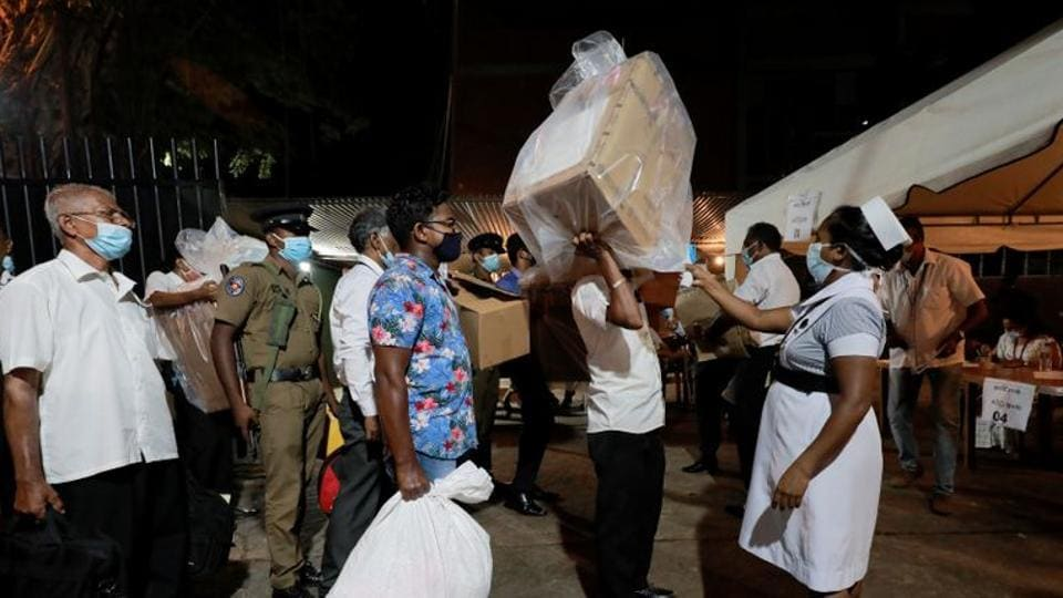 A health official takes the temperature of election officials who arrive with ballot boxes from a polling station to a counting center, after the voting ended during the country's parliamentary election in Colombo, Sri Lanka.