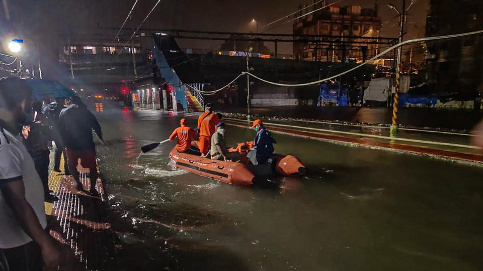 NDRF personnel rescue passengers from a local train stranded between Masjid Bunder and Byculla stations on the Central line, during heavy rain in Mumbai on Wednesday.