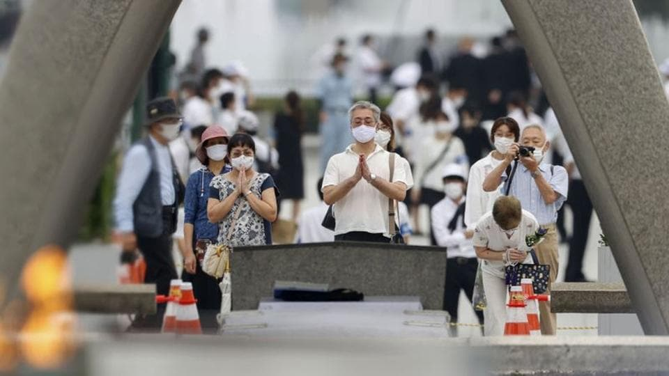 People wearing protective face masks pray for atomic bomb victims in front of the cenotaph for the victims of the US 1945 atomic bombing, at Peace Memorial Park in Hiroshima, western Japan, August 6, 2020, on the 75th anniversary of the atomic bombing of the city.