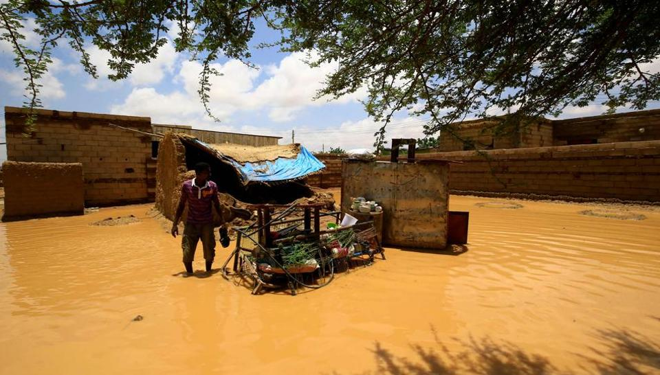 A Sudanese man stands next to the belongings of a house, after torrential rain lead to landslides and flash floods, in the town of Umm Dawan Ban, southeast of the capital Khartoum on August 2, 2020.