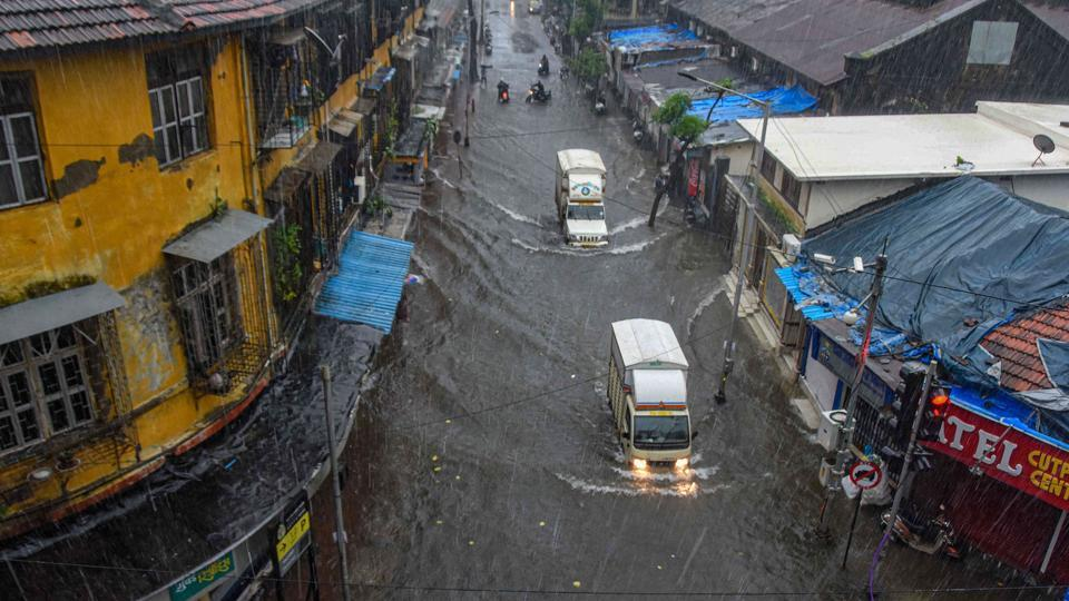 Vehicles ply on a waterlogged street during heavy rains, at Byculla area in Mumbai.
