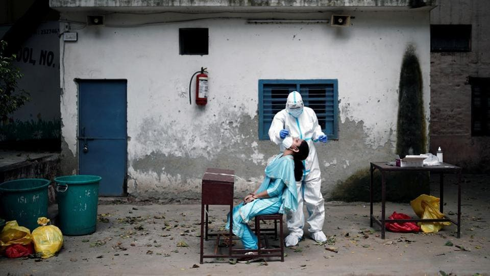 A health worker in personal protective equipment (PPE) collects swab sample from a person to test for coronavirus infection in New Delhi on August 6. Union health ministry's data released on August 7 morning showed that India reported more than 62,000 Covid-19 cases taking its tally past 2 million.  (Adnan Abidi / REUTERS)