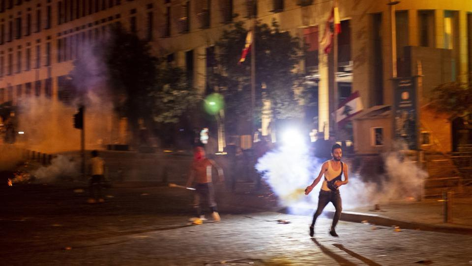An anti-government protester throws back a tear gas canister fired by the riot police during a protest against the Lebanese political leadership after the massive explosion, in Beirut on August 7.  (Hassan Ammar / AP)
