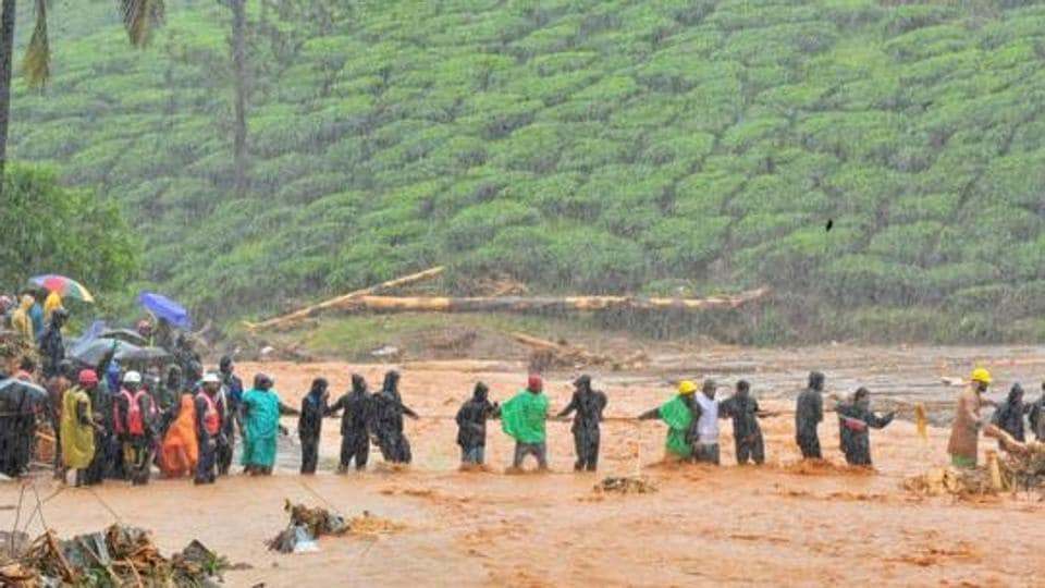 Rescuers help people to cross a flooded area after a landslide caused by torrential monsoon rains in Meppadi in Wayanad district of Kerala on August 9, 2019.