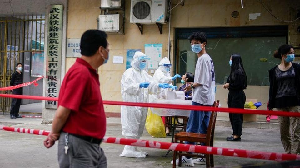 Medical workers in protective suits conduct nucleic acid testings for residents at a residential compound in Wuhan.