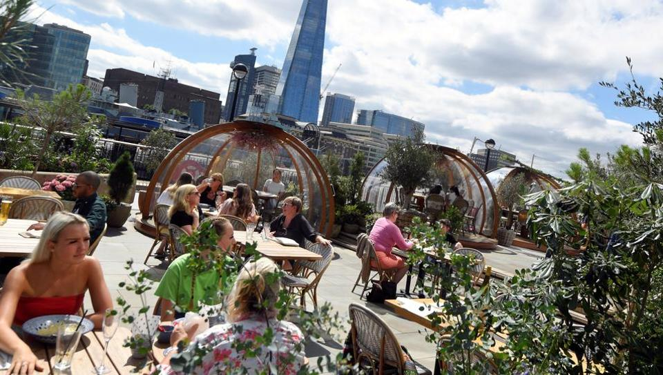 People eat outside and inside private dining pods, on the terrace of a restaurant,  in London, Britain, August 6, 2020.