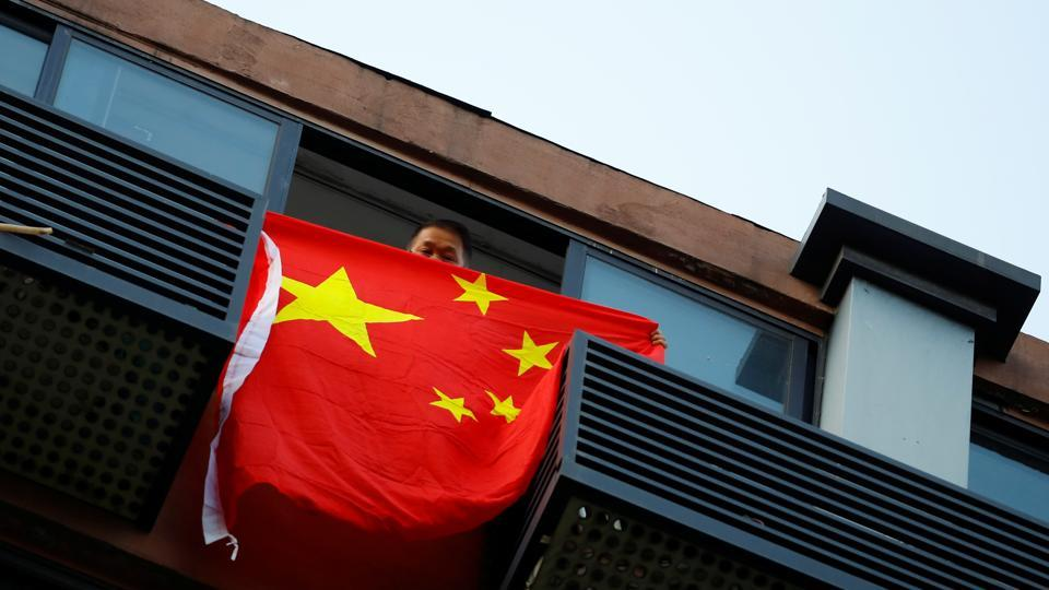 A man holds a Chinese flag from a house opposite the U.S. Consulate General in Chengdu, Sichuan province, China.