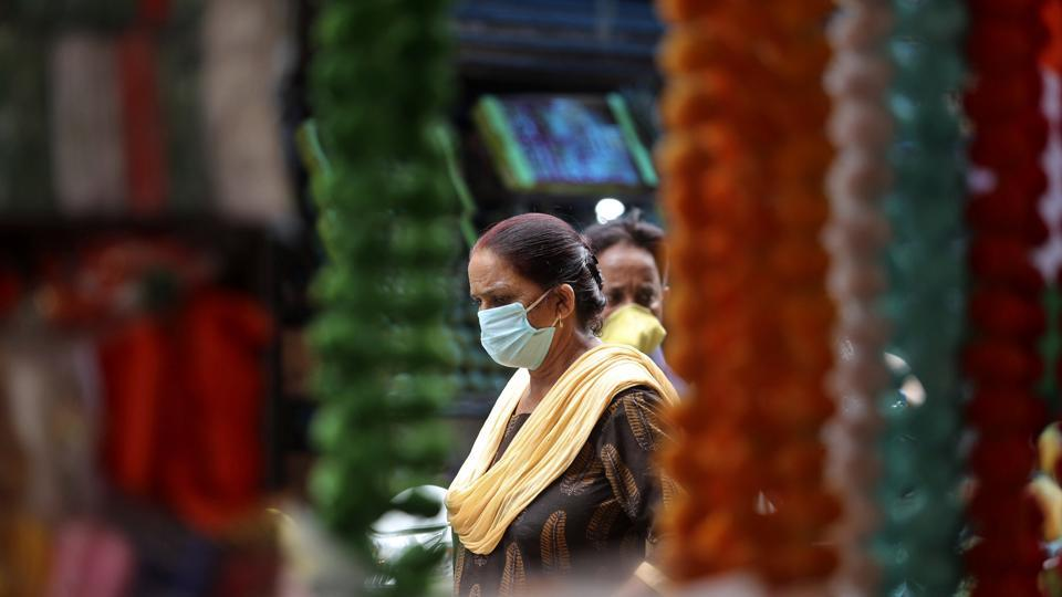 Women wearing face masks as a precaution against the coronavirus walk at market in Jammu.