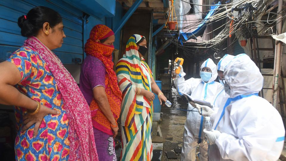 BMC health worker and doctors  on Covid-19 duty conduct thermal screening and pulse test of a resident in Mumbai's Dharavi on Saturday.