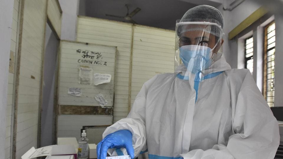 A health worker in PPE kit shows a coronavirus testing slide.