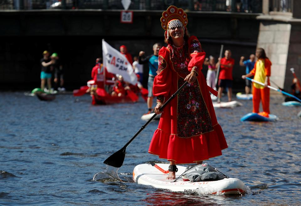 A participant makes her way on the Griboyedov Canal during the Fontanka-SUP stand up paddle boarding festival in Saint Petersburg, Russia August 8, 2020.  (REUTERS)