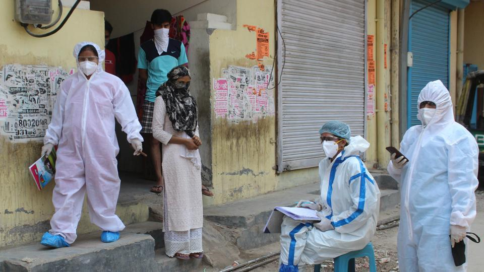 Medical workers in PPE overalls during a screening exercise during a nationwide lockdown due to coronavirus pandemic.
