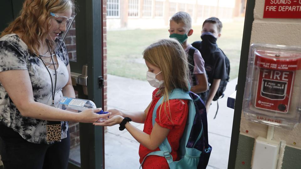 Wearing masks to prevent the spread of Covid-19, elementary school students use hand sanitizer before entering school for classes in Godley, Texas. As schools reopen around the country, their ability to quickly identify and contain coronavirus outbreaks before they get out of hand is about to be put to the test.