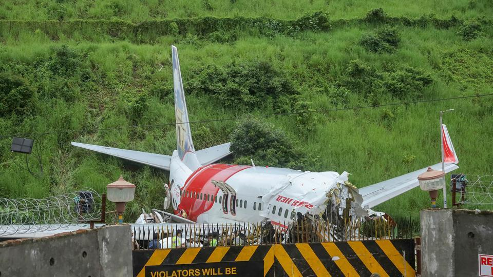 Security personnel stand guard near the mangled remains of an Air India Express flight, en route from Dubai, after it skidded off the runway while landing on Friday night, at Karippur in Kozhikode on August 08, 2020.