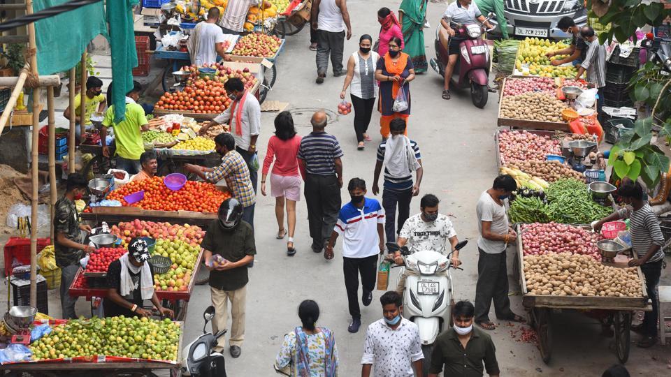 Vendors and customers are seen wearing face masks as a precaution against the coronavirus (Covid-19) disease in Pandav Nagar, New Delhi on Friday.