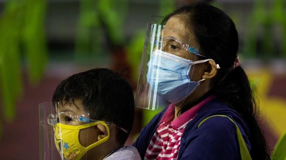 A woman and a child wearing a protective face shield and mask queue for free coronavirus disease (COVID-19) swab testing at a gymnasium in Navotas City, Metro Manila, Philippines.