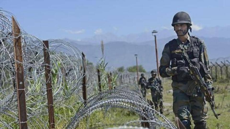 An Indian Army soldier patrols on the fence near the India-Pakistan LoC in Chakan-da-Bagh area near Poonch.
