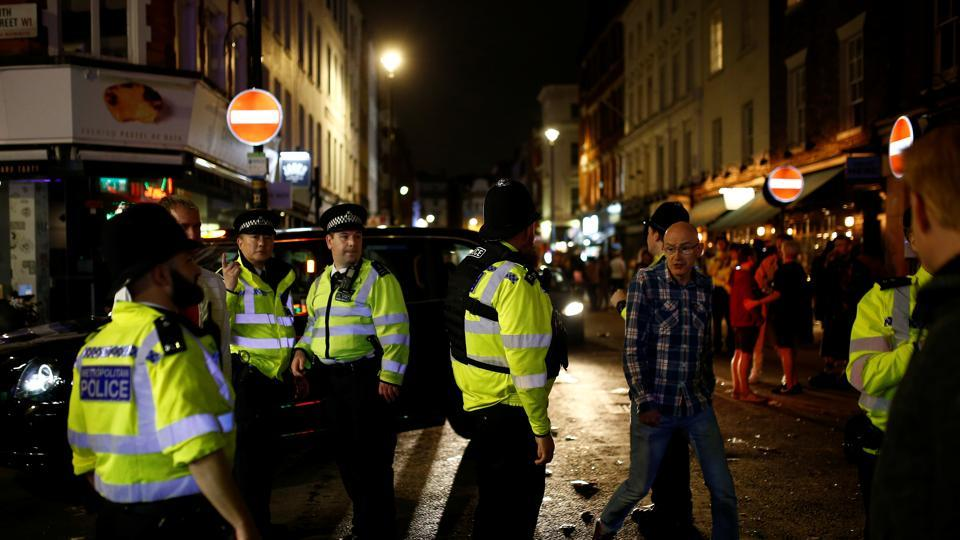 Police on patrol as people gather in Soho, in London.