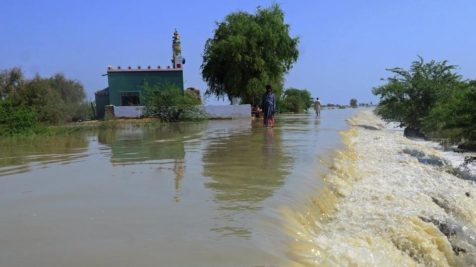 Villagers wade through a flooded area of Dadu, a district in Pakistan's southern Sindh province, Sunday.