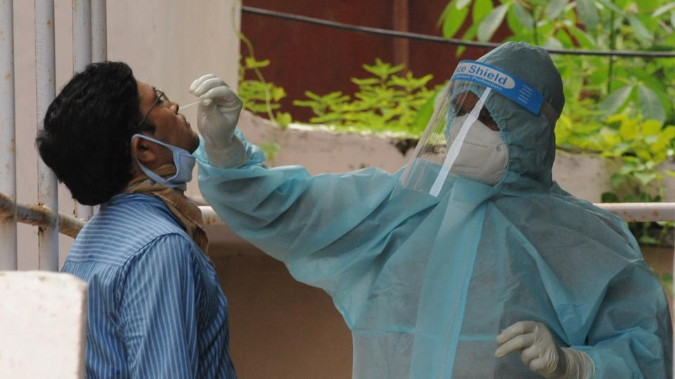 A health worker in PPE kit collects a swab sample from a man for a coronavirus test, at a Covid-19 dedicated health centre, in Patna, Bihar. ( Photo by A P Dube/Hindustan Times)