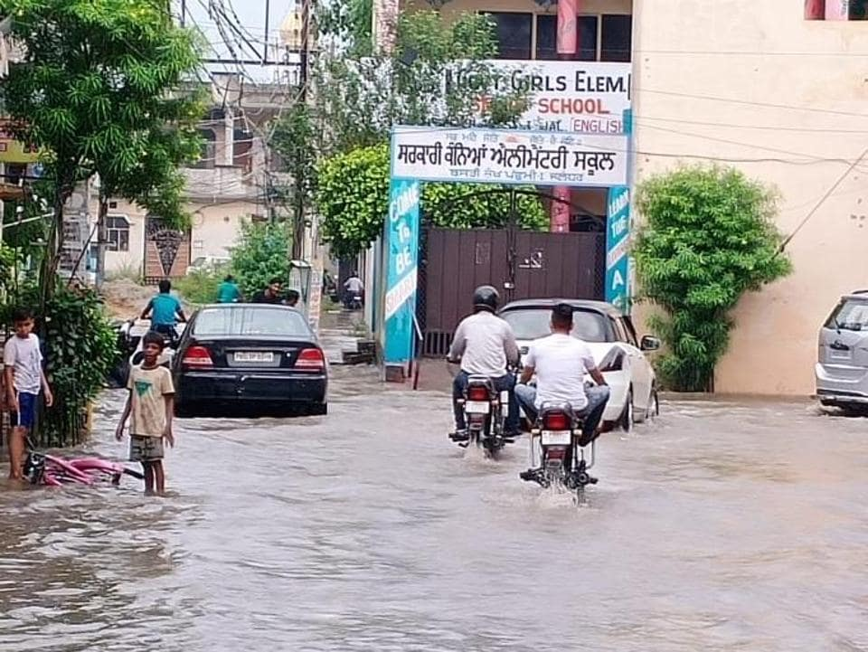 Commuters making their way through a waterlogged street in Basti Sheikh locality of Jalandhar on Monday morning.