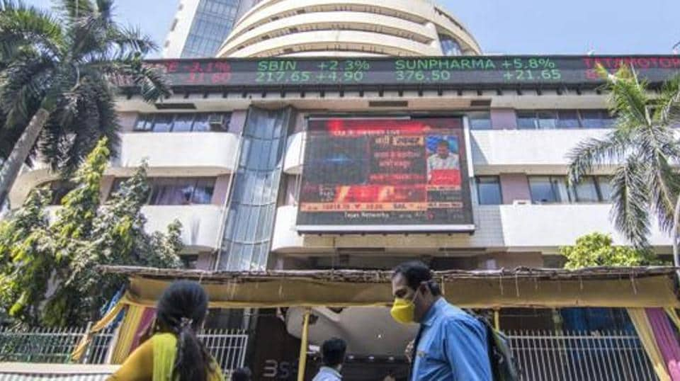 A man walks wearing a mask next to the Bombay stock exchange building.
