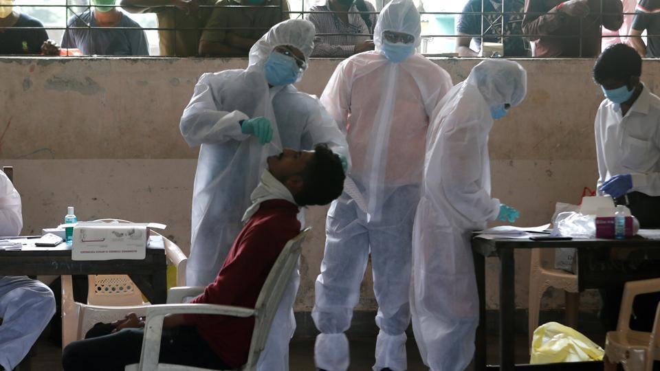 A health worker in personal protective equipment (PPE) collects a swab sample from a man.