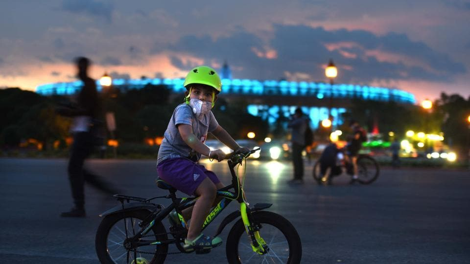 A child cycles outside the Parliament House during sunset in New Delhi on August 06, 2020.