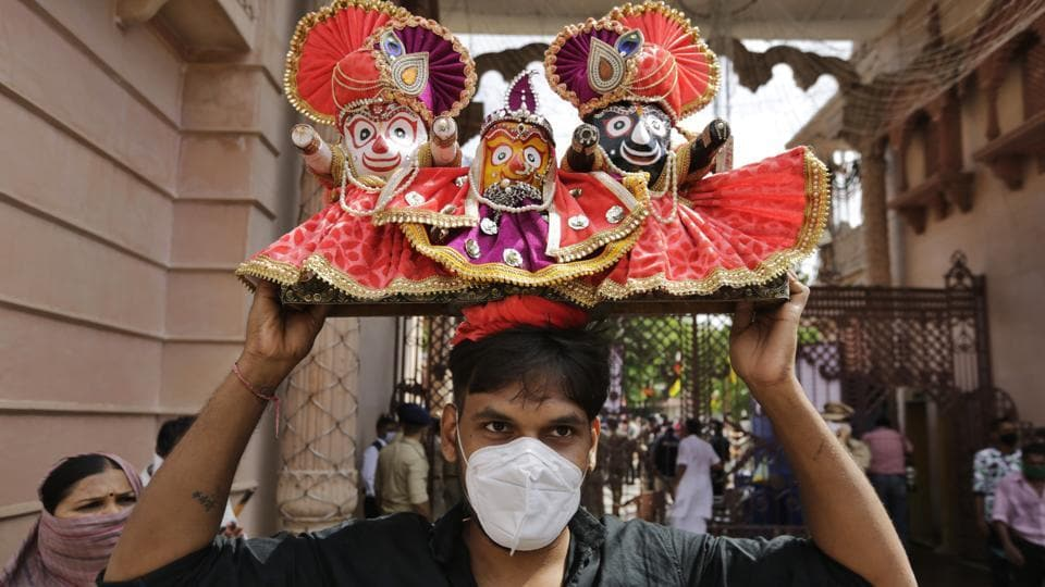 A Hindu devotee wearing a mask carries on his head an idol that depicts Lord Jagannath flanked by sister Subhadra and brother Balram during the annual chariot procession of Lord Jagannath in Ahmedabad.