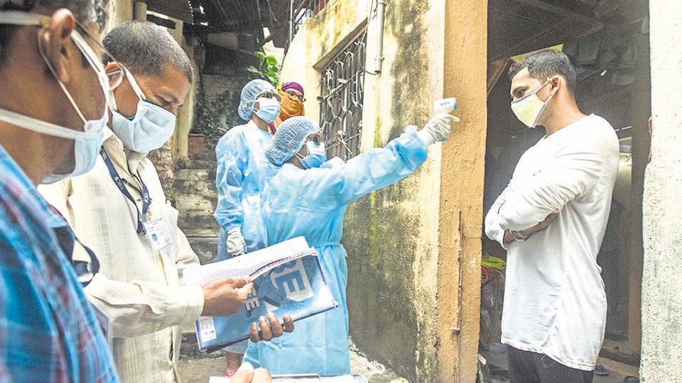 Healthcare workers carry out door-to-door thermal screening at Janata vasahat in Pune on August 10.