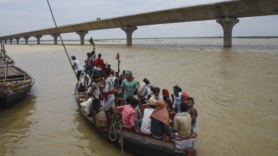 Villagers travel through the swollen Ganga river on a boat, in Patna.