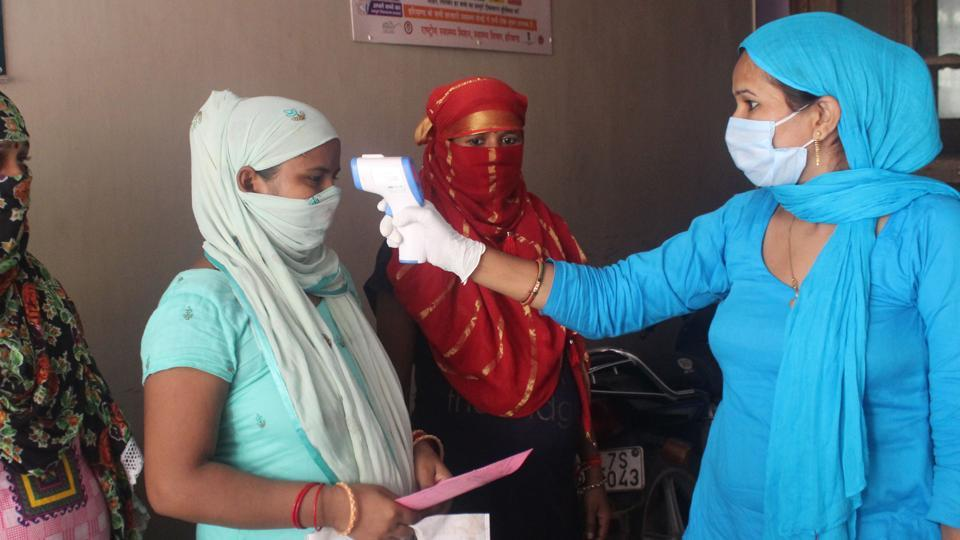 A health worker uses an infrared thermometer to screen a woman during swab sample collection for Covid-19 testing in Gurugram  on Monday. India's Covid-19 tally has now surged to more than 2.26 million, data showed on Tuesday.