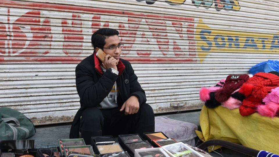A man speaks on a mobile phone at a marketplace in Srinagar, Jammu and Kashmir.