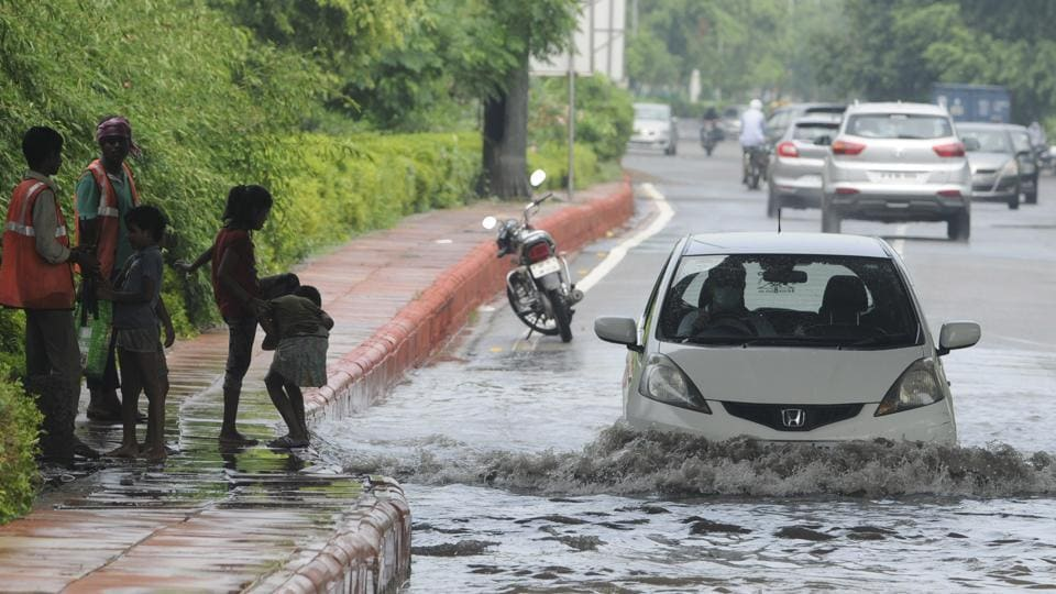 A car passes through a heavily waterlolgged stretch at Sector 44, in Noida.